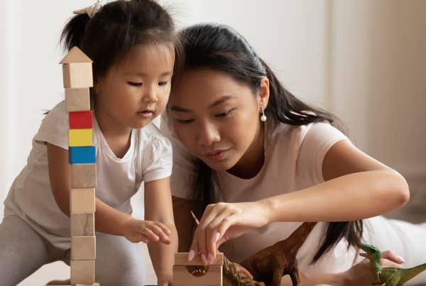 Mother and daughter have playtime together with toys