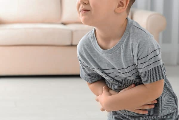 young boy holds sore stomach due to constipation
